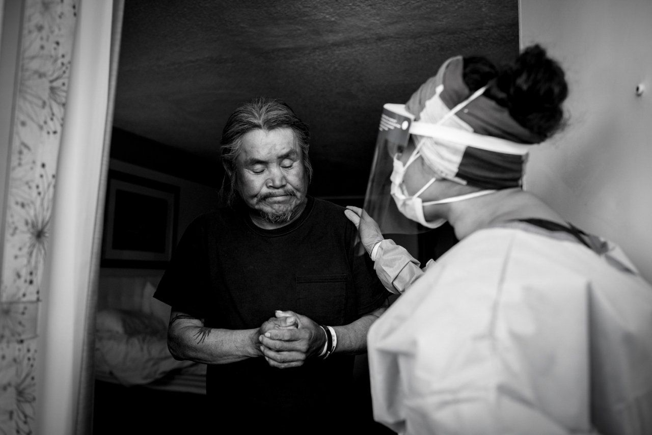 doctor talks with man in a hotel doorway