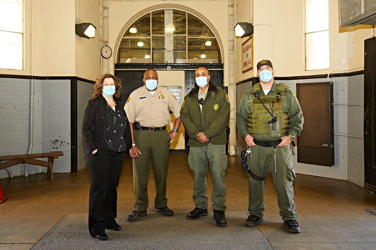 Photo of Brie Williams and correctional officers at San Quentin State Prison.