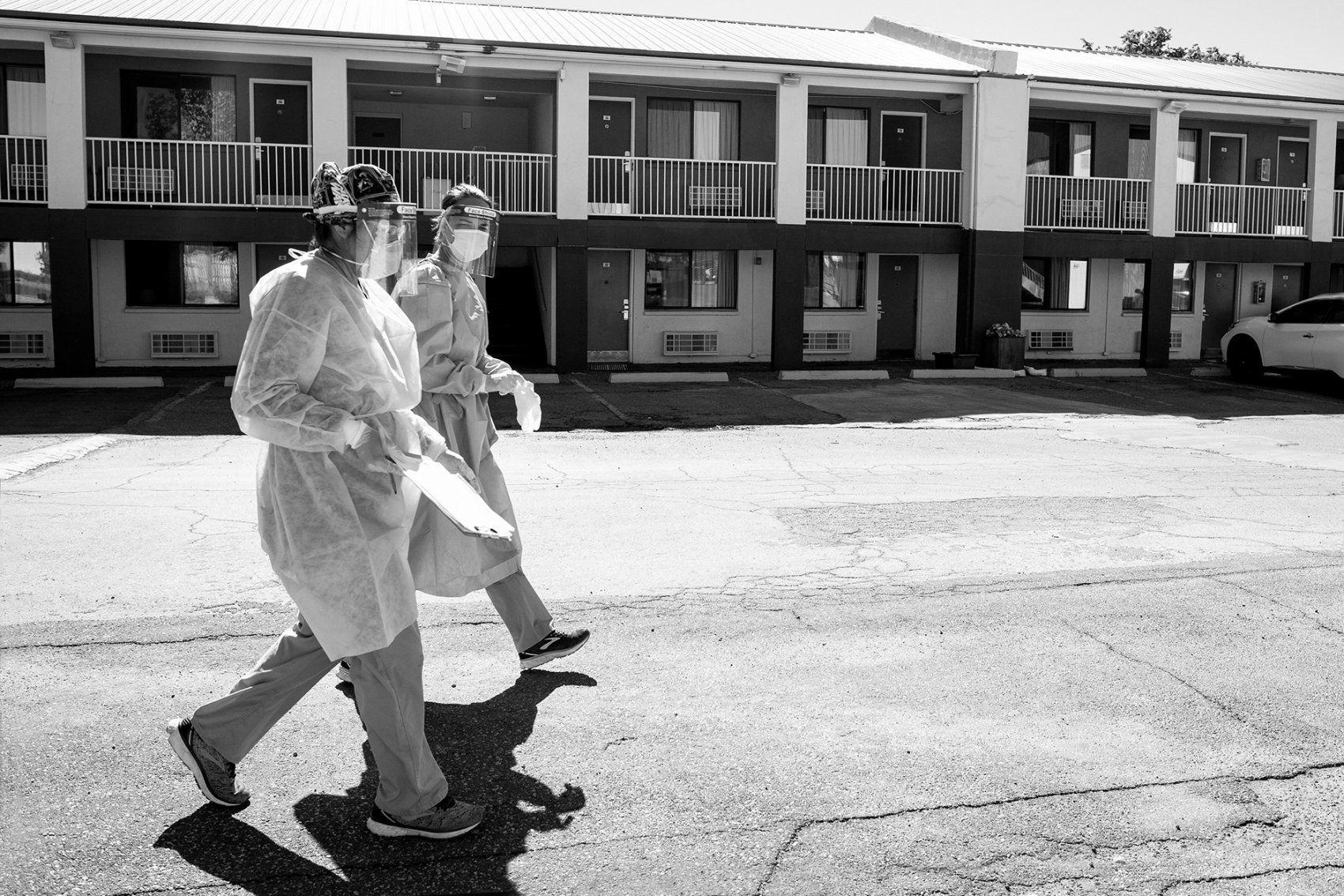 medical workers walk across a motel parking lot