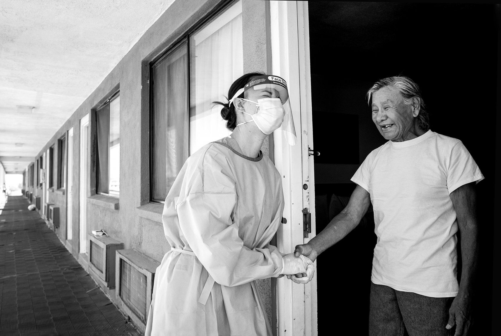 medical worker talks with a man in a motel doorway