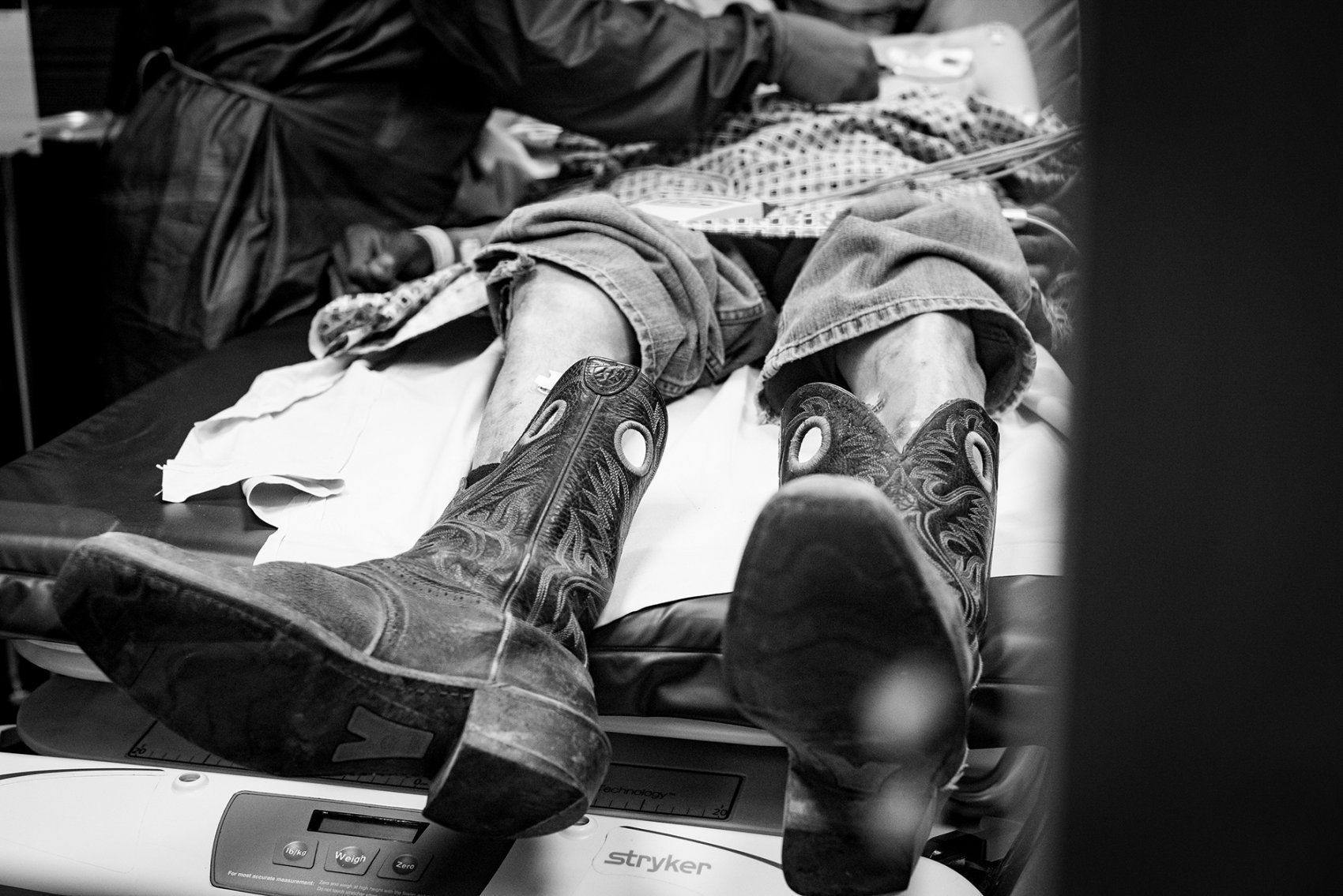 patient with cowboy boots on lies on a triage medical table