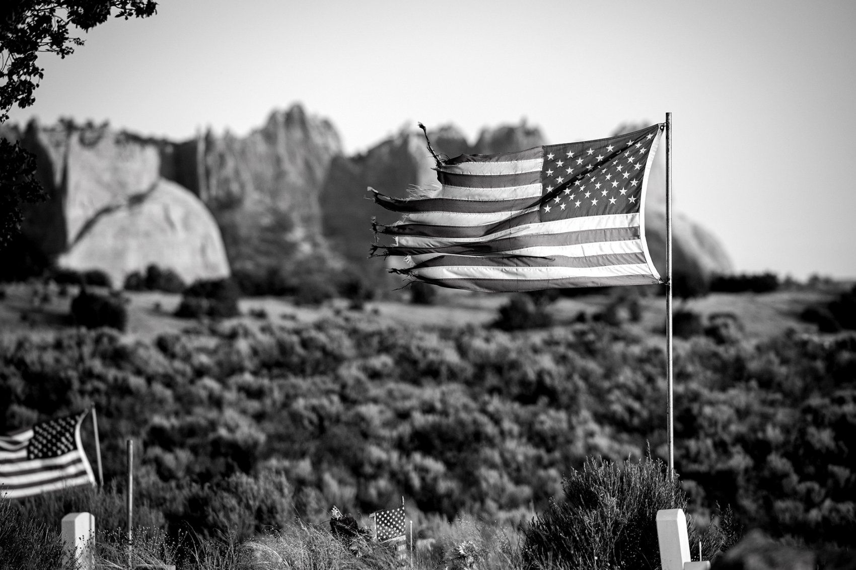 tattered flag flies over a cemetary