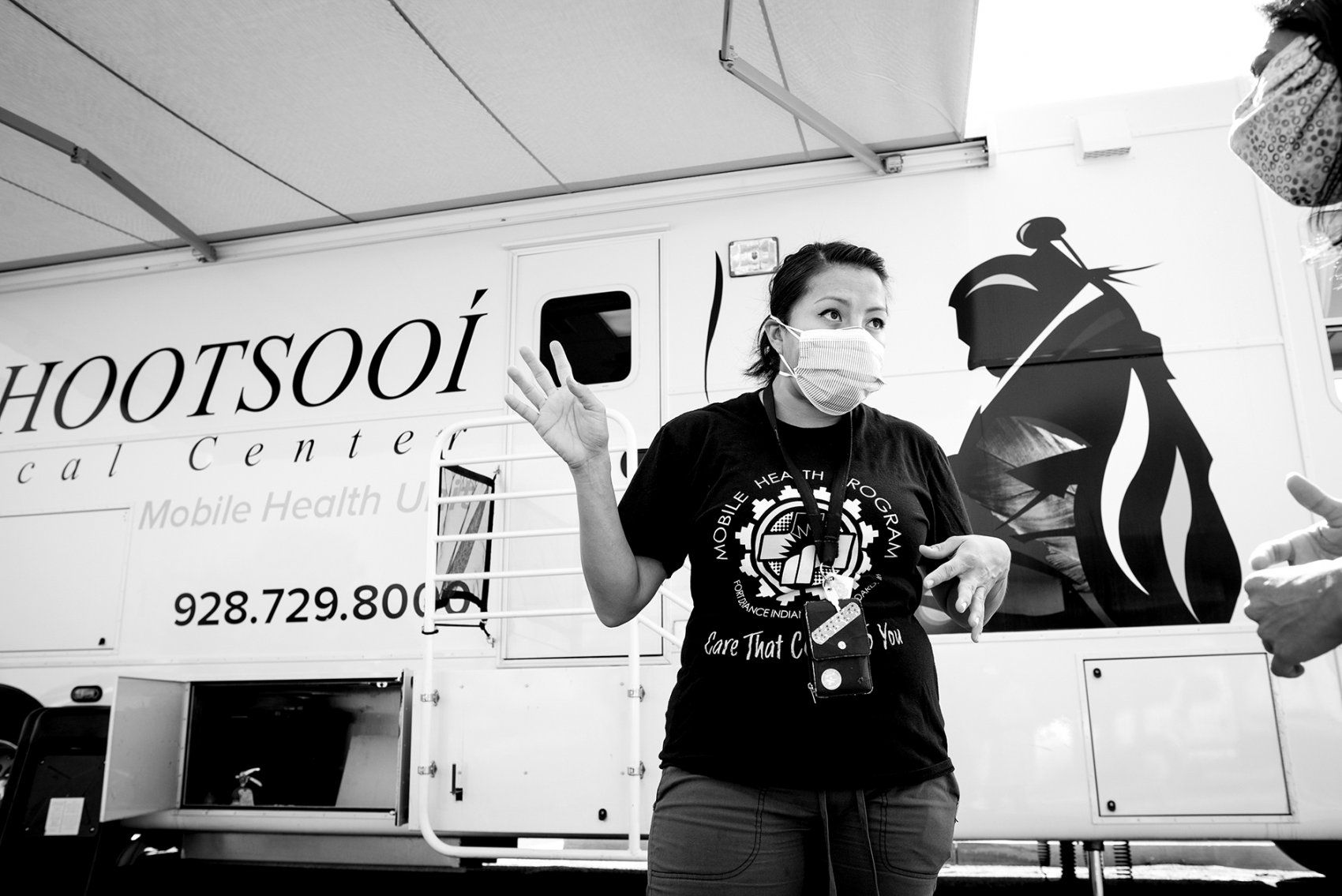 a female health care worker talks in front of a mobile clinic