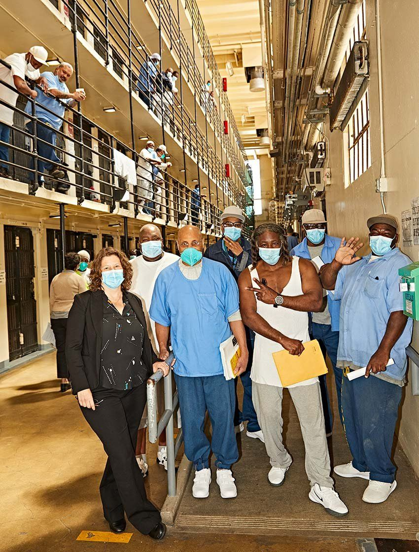Photo of Brie Williams with incarcerated men at San Quentin State Prison.
